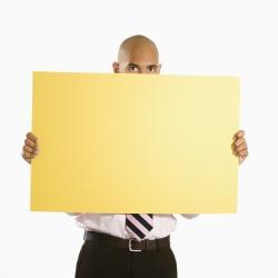 Businessman holding blank sign.