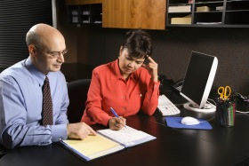 Businessman and businesswoman in office going over appointment calendar.