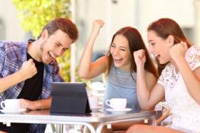 Junge Leute betrachten ein Tablet und freuen sich