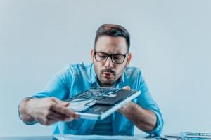Mann repariert und reinigt Notebook
